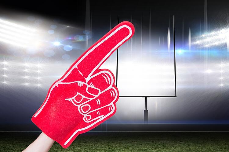 American football player holding supporter foam hand against american football arena.jpeg