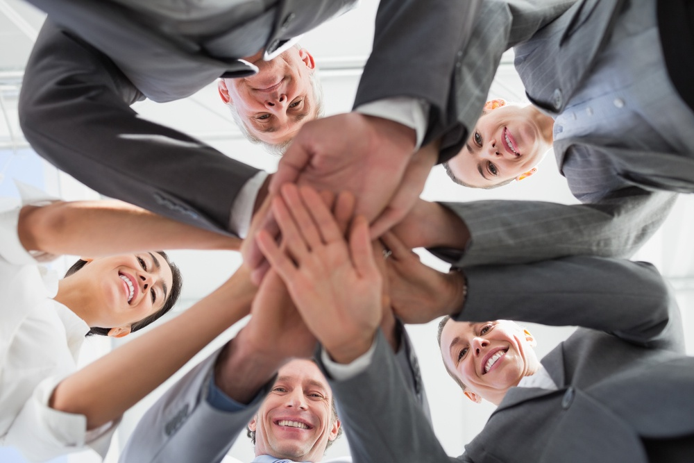 Business team standing hands together in the office.jpeg