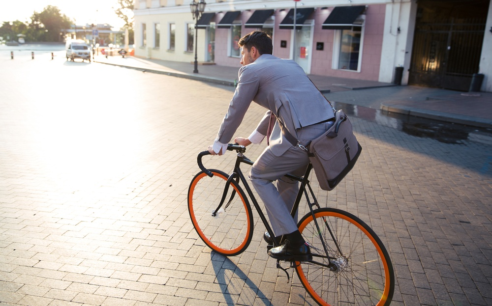 Businessman riding bicycle to work on urban street in morning.jpeg