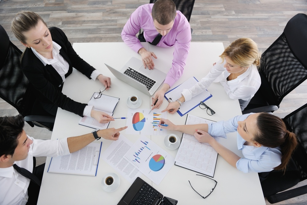 Group of young business people sitting in board room during meeting and discussing with paperwork.jpeg