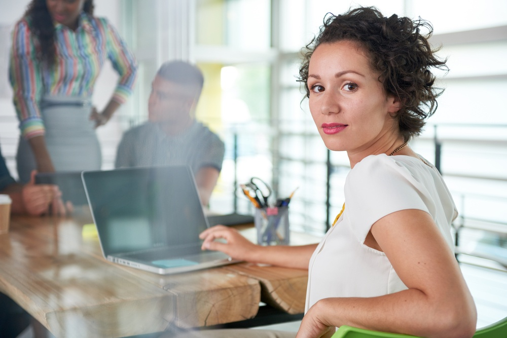 Image of a succesful casual business woman using laptop during meeting-2