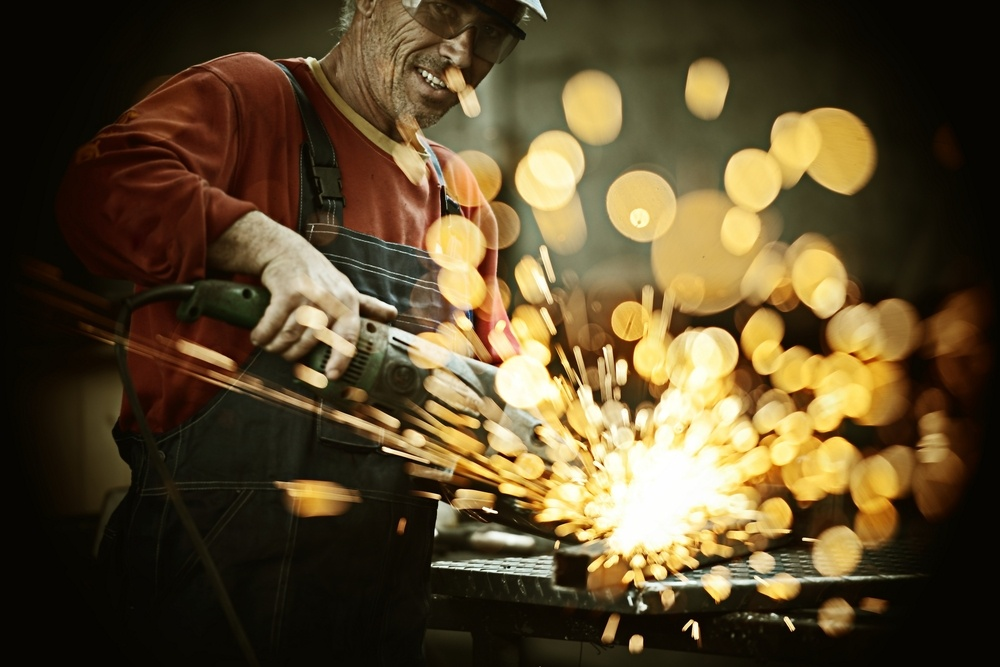 Industrial worker cutting and welding metal with many sharp sparks.jpeg