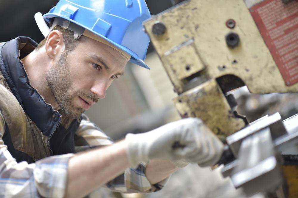Industrial worker working on machine in factory.jpeg