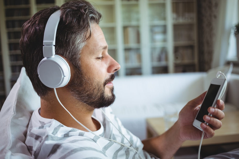 Man listening to music on headphones at home