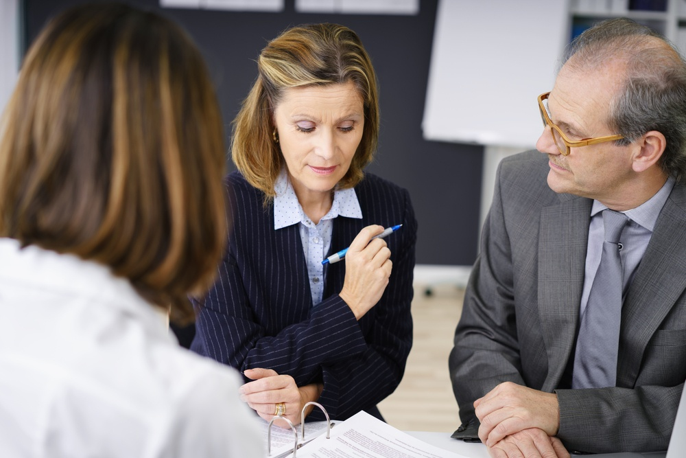Middle-aged couple planning for retirement in a meeting with a female broker or investment adviser in her office-2
