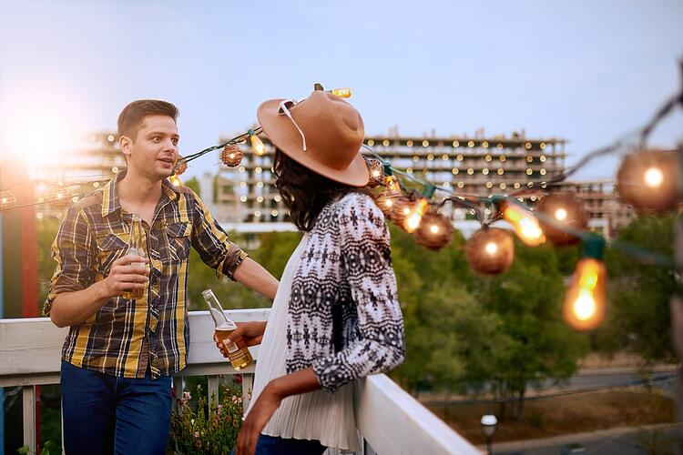 Multi-ethnic millenial couple flirting while having a drink on rooftop terrasse at sunset.jpeg