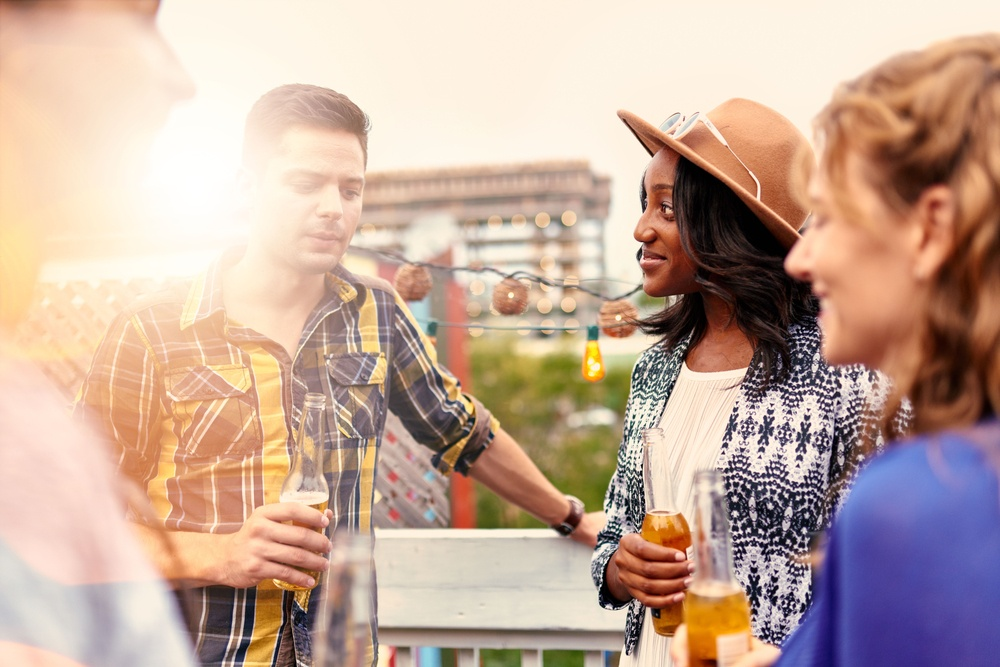 Multi-ethnic millenial group of friends partying and enjoying a beer on rooftop terrasse at sunset