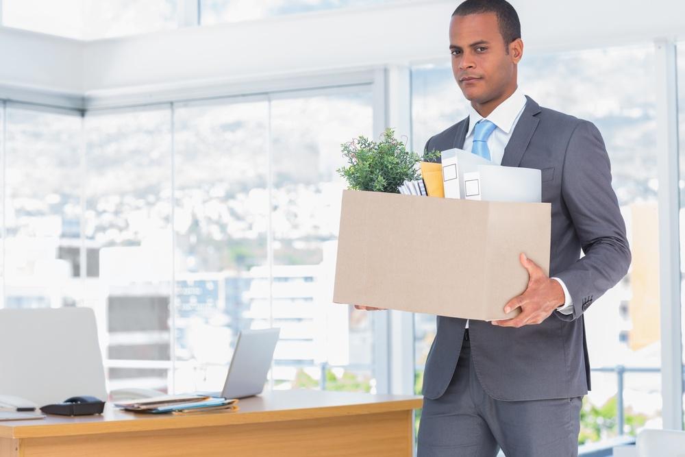 Sad businessman leaving his company while he is holding a box.jpeg
