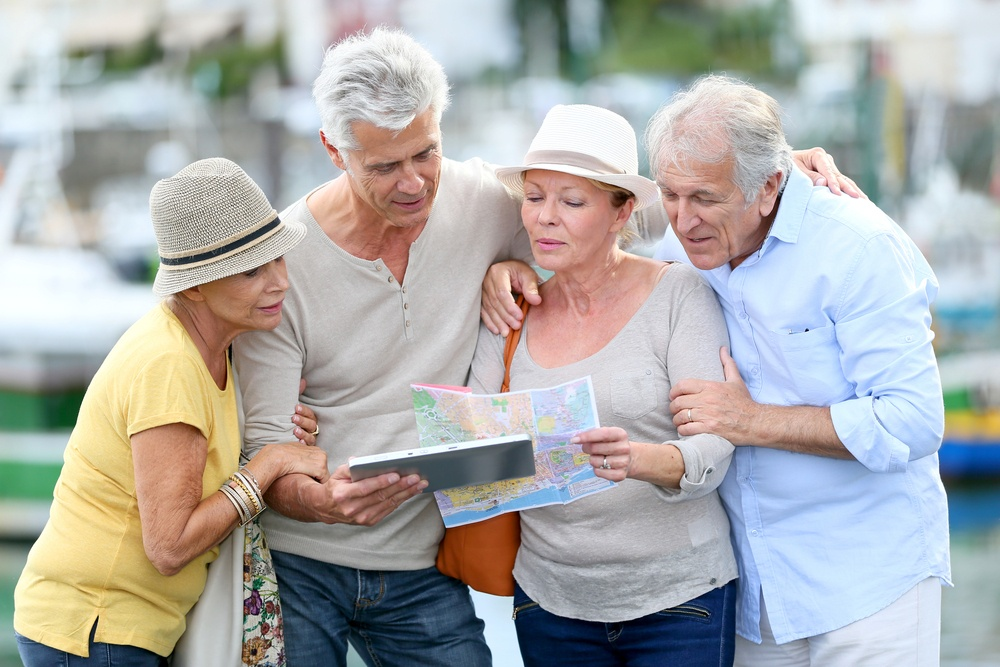 Senior tourists using tablet on visiting journey.jpeg
