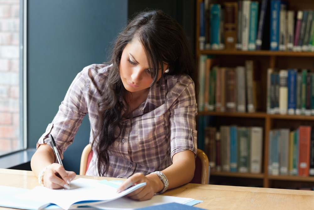 Young student writing in a library