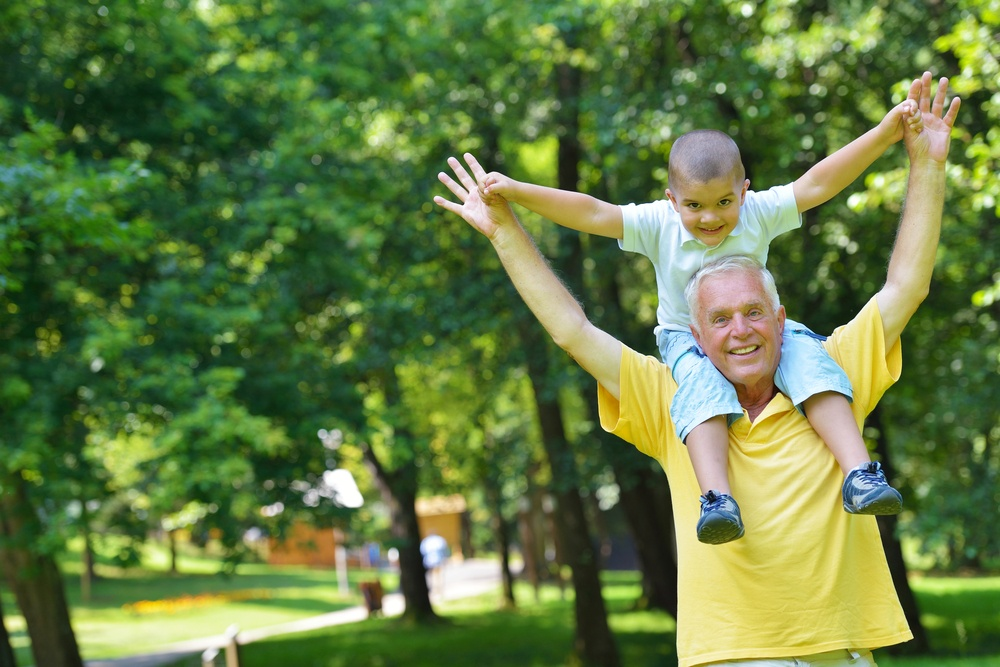happy grandfather and child have fun and play in park.jpeg