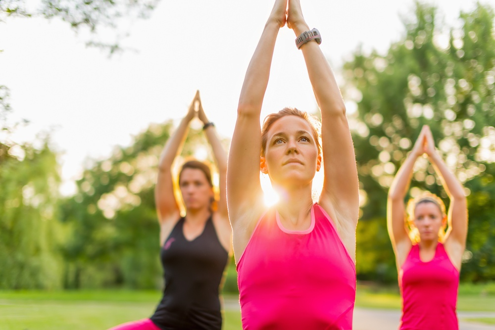 horizontal detail of women doing yoga outdoors at sunset with lens flare. Defocused.jpeg