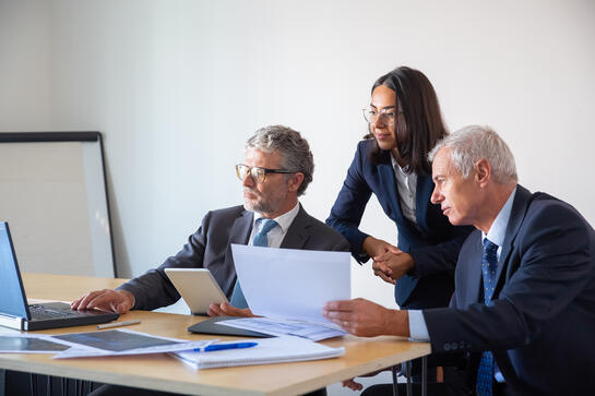 concentrated-partners-using-laptop-working-with-documents-confident-serious-businesspeople-office-suits-discussing-company-project-together-management-business-partnership-concept