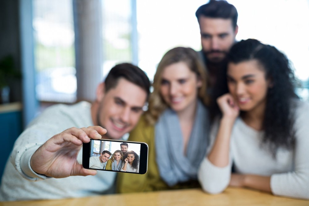 Group of friends taking a selfie in cafe-3