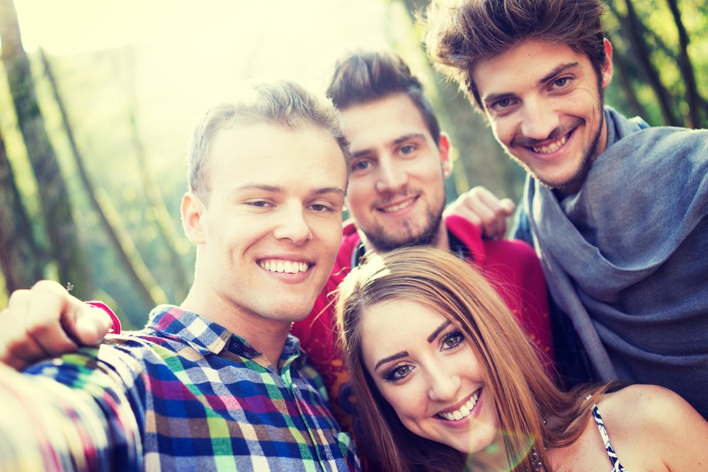 Young people having good time together in park on river and taking selfie-4