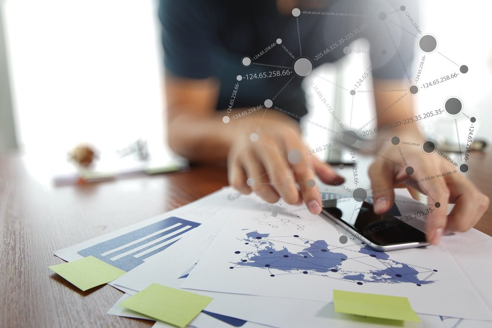 business documents on office table with smart phone and digital tablet and man working in the background-1