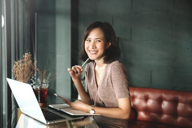 young-business-woman-sitting-at-table-in-cafe-and-writing-in-notebook-student-computer-freelancer_t20_pRBl2d