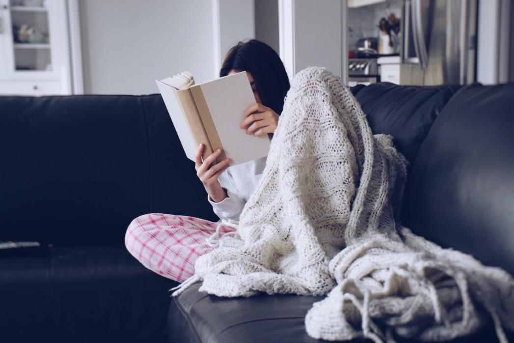 young-teenage-girl-sitting-on-a-couch-with-a-cozy-blanket-and-reading-a-book-nominated_t20_gRGj9d